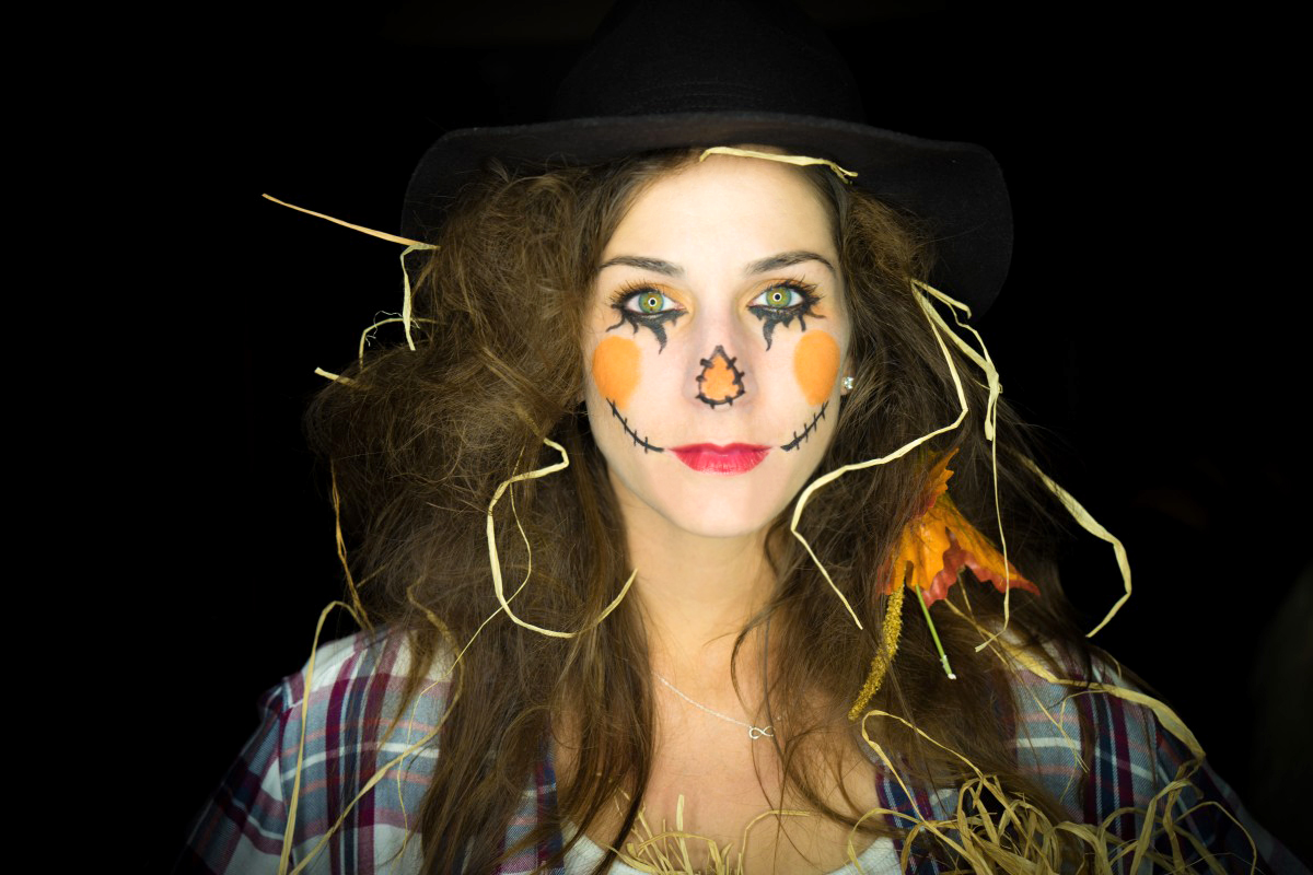 Woman in face paint as scarecrow